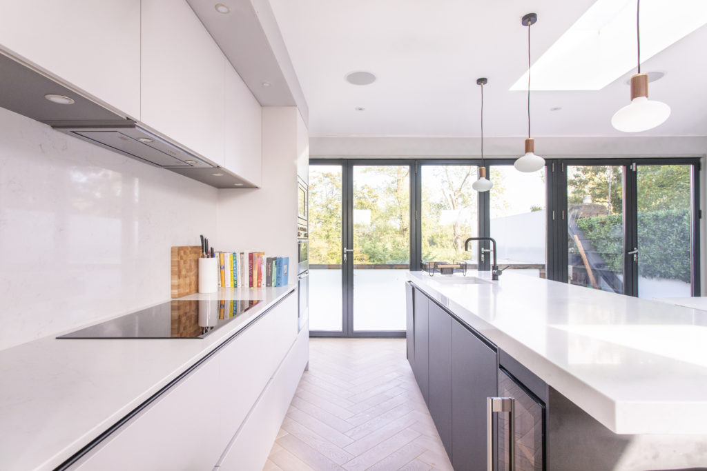 Balham Kitchen with white and dark blue handleless matt lacquer kitchen cabinets and island looking towards alumium bi-fold doors.