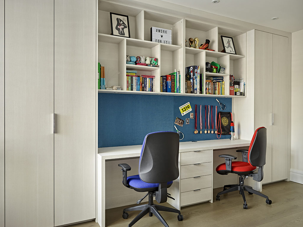 Light and bright kids study area with double desk, storage cabinets and built-in display shelves