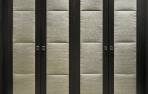 Luxury fitted wardrobes with dark wood exterior with padded, upholstered panels.