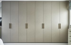Minimalist wall of floor to ceiling fitted wardrobes in natural brown / cream tones with long, straight wooden handles
