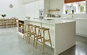 Scandi Style white kitchen island with built in bookcase and bar stools in light wood finish with dining area in the background