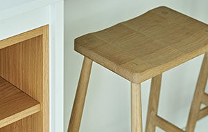 Close up of light wood accents in scandi style kitchen design - island bookshelves and barstools