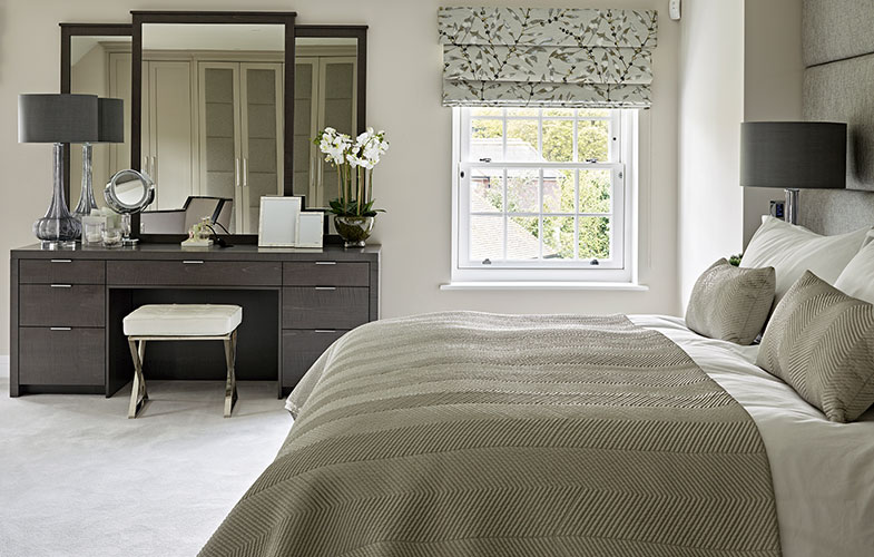 Luxury master bedroom with upholstered headboard, bespoke dressing table with 3 large framed mirrors