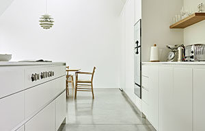 White minimalist kitchen design with Island integrated hob and wall mounted ovens by Gaggenau
