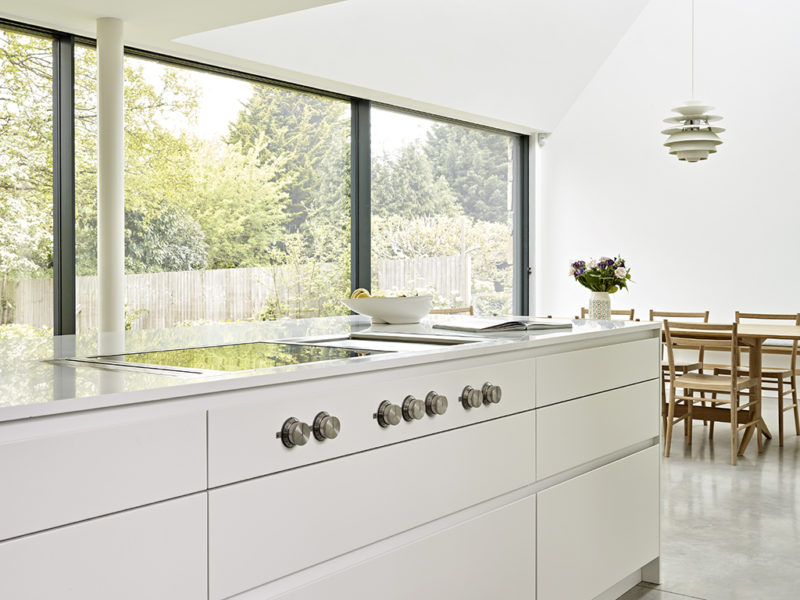 Island and dining area of scandi style kitchen with glass wall looking out into garden