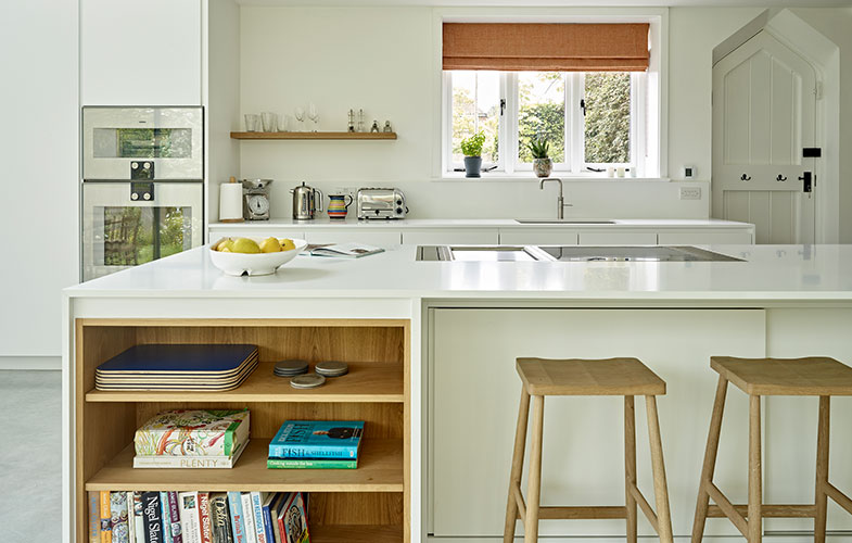 Scandi Style kitchen with white minimalist cabinets and light wood accents, kitchen island, chapel style door and integrated Gaggenau appliances