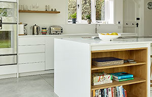 White kitchen island with built in cookbook bookcase in light wood finish.