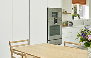 Scandi style kitchen design with minimal handleless cabinets and wall mounted appliances by Gaggenau