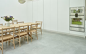 White handleless full-length kitchen cabinets in a minimalist style for Scandi Style kitchen with concrete floor.