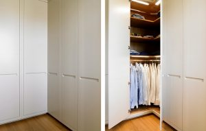 Custom corner wardrobes minimalist futuristic design in cream/grey. Natural wood interior, automatic lighting, organised shelving and low shirt rail.