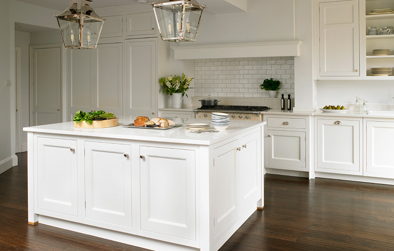 New England style kitchen with white shaker cabinets and dark hardwood floors. Chimney recess with range cooker, lantern lighting and country style cabinetry