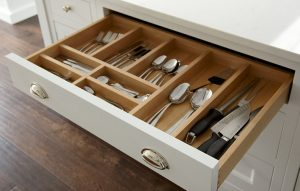 Wide white island cutlery drawer with cup handles and light wood interior