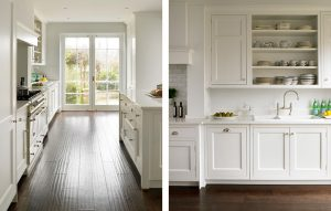 White shaker kitchen with dark wood floors looking out through french doors and open cabinet with shelves for plate storage.