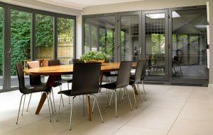 Wine room and display cabinetry joined to dining room/orangery space with closed glass doors.