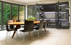 Modern wine room/display cabinets adjoined to dining room in orangery with open glass doors.