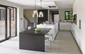 White modern kitchen design with large island with dining table attached.