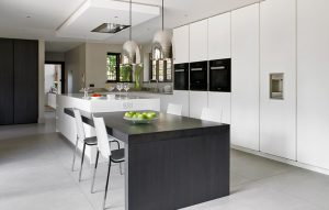 Contemporary white handleless kitchen design featuring island with integrated dining table