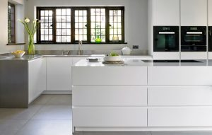 Modern minimalist white kitchen with stainless steel worktops and island with drawer storage