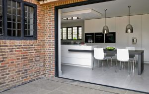 Exterior of white modern kitchen design looking through open folding glass doors.