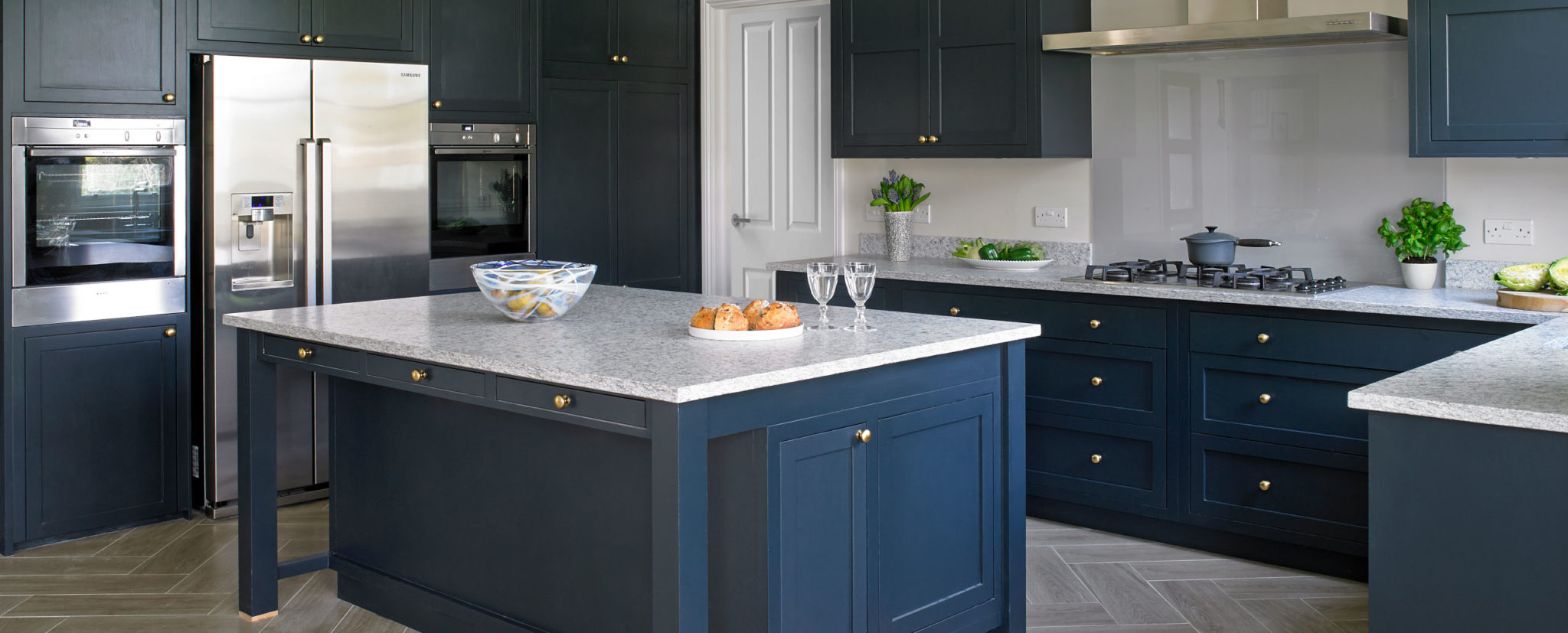 Contemporary shaker kitchen with dark blue cabinets, grey granite worktops, stainless steel appliances and light hardwood chevron flooring.