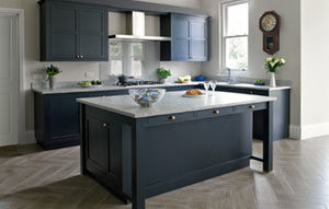 Dark blue kitchen design with shaker cabinets, kitchen island, grey granite worktops and chevron parquet wooden floor.