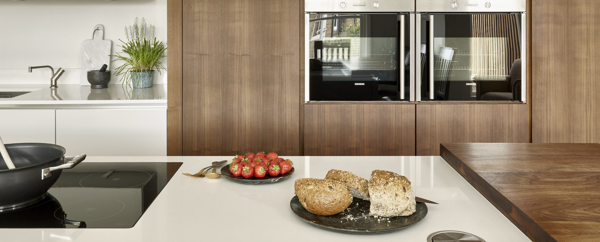 Kitchen island worktop with integrated electric hob. Handleless walnut kitchen cabinets with wall-mounted oven.