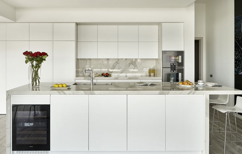 Handleless white minimalist penthouse kitchen in London with large island