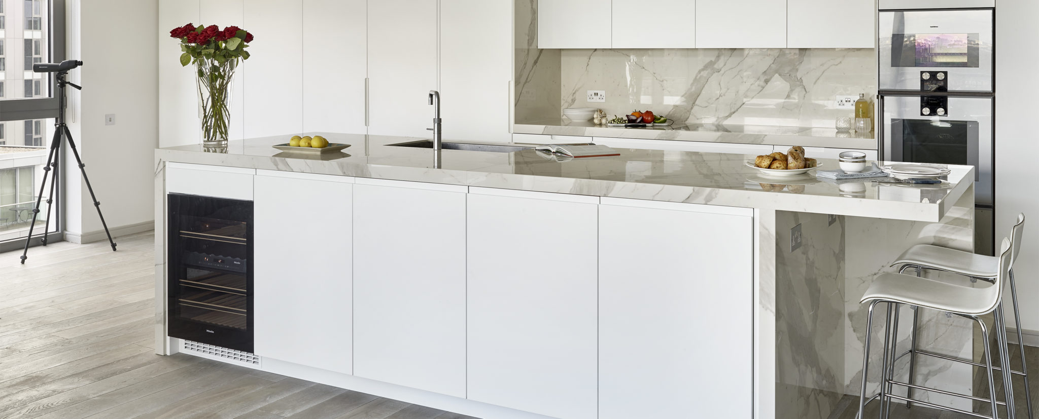 Modern penthouse kitchen for riverside apartment in Wandsworth London - handleless white matt lacquer kitchen cabinets with Laminam Staturio effect marble island, splashback and worktops