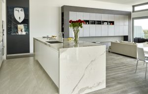Open plan penthouse renovation, modern marble effect kitchen island and media wall with grey Xylocleaf surfaces