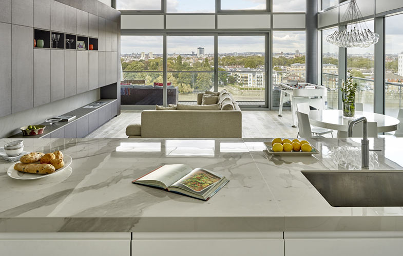 View from kitchen island of open plan London penthouse with dining area and media wall design