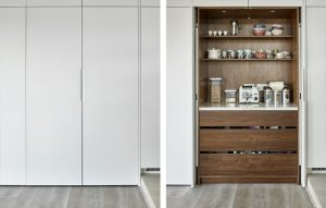 Concealed pantry/breakfast cupboard - white minimalist exterior cabinets with American black walnut interior