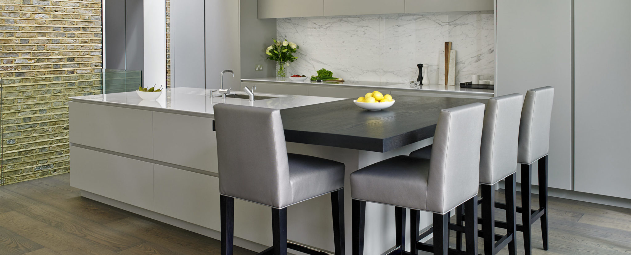 Handless kitchen design with silver matt grey lacquered cabinets with large island and attached elevated breakfast bar in charcoal oak with custom made upholstered stool seating