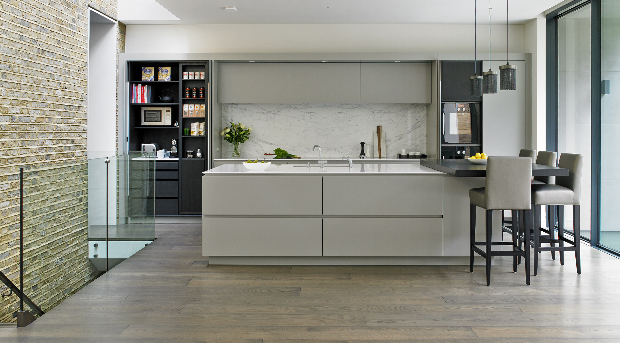 Modern handleless kitchen design for Victorian family home in Wandsworth with silver grey matt-lacquered cabinets with pure white composite worktops, Calacatta marble splashback, island with breakfast bar and pantry cupboard.