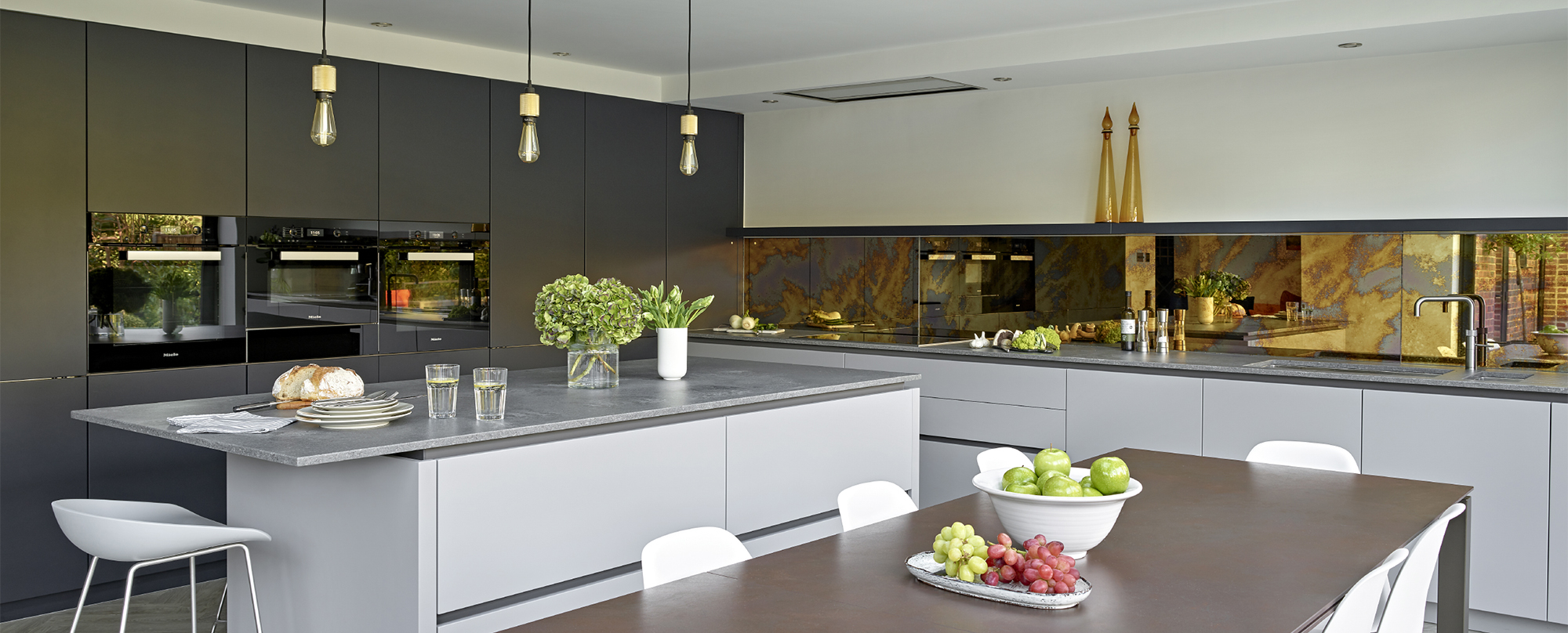 Chobham Modern kitchen dining room design with inky blue and mid grey handleless cabinets, rustic concrete quartz worktops and antique bronze mirror splashback.