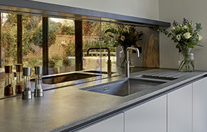 Antique bronze mirrored splashback for Chobham Kitchen with Quooker Fusion 3 in 1 tap, Rugged Concrete countertops by Caesarstone and flat panel cabinets in matt mid grey.