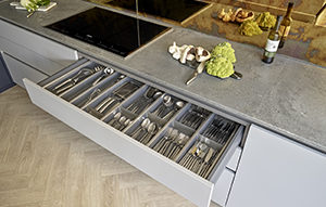 Cutlery drawer for Chobham kitchen with satin matt-lacquered furniture in mid grey and Caesarstone Rugged Concrete countertops and induction hob by Miele.