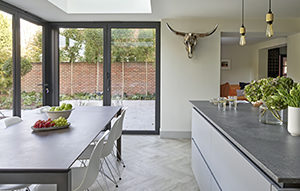 Island and dining area of Chobham kitchen with 'Rustic Concrete' worktops and mid-grey satin matt lacquered cabinetry and 'Laurel Oak' Moduleo herringbone flooring.