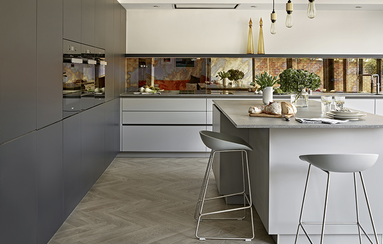 Inky blue handle-less tall cabinets and mid-grey drawers and island for Chobham kitchen design with mirror backsplash and rustic concrete quartz worktops.