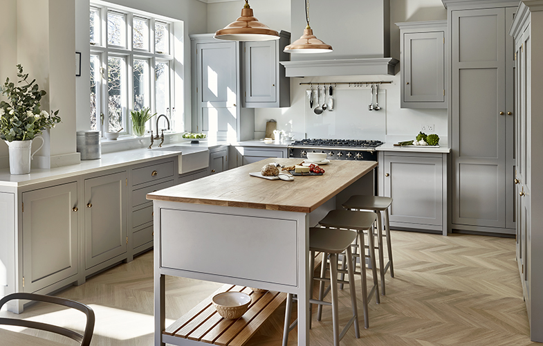 Light Grey shaker style country kitchen, chevron oak flooring and copper island lighting.