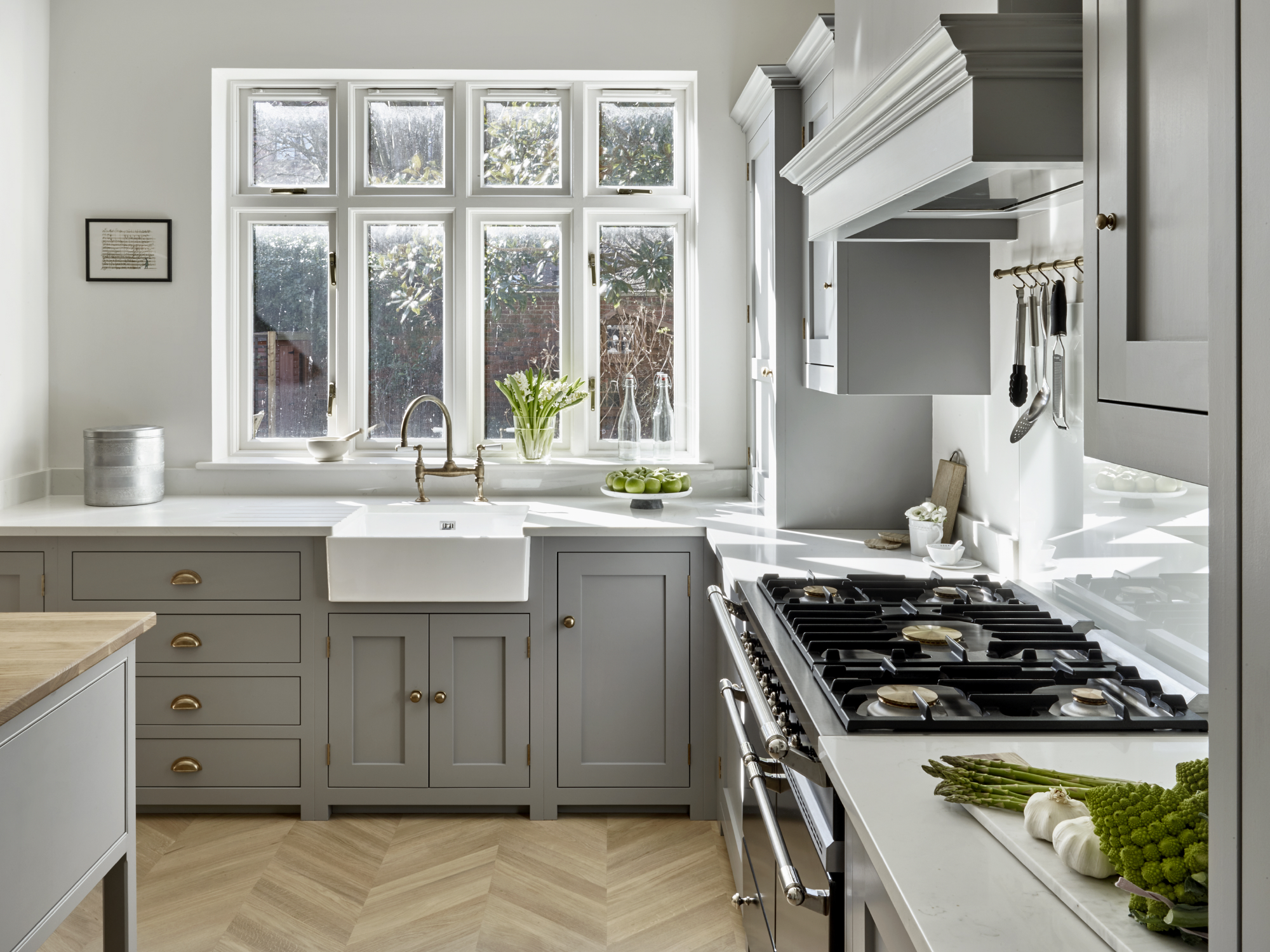 Grey country kitchen by Brayer Design with shaker cabinets, butlers sink and chevron wood floor