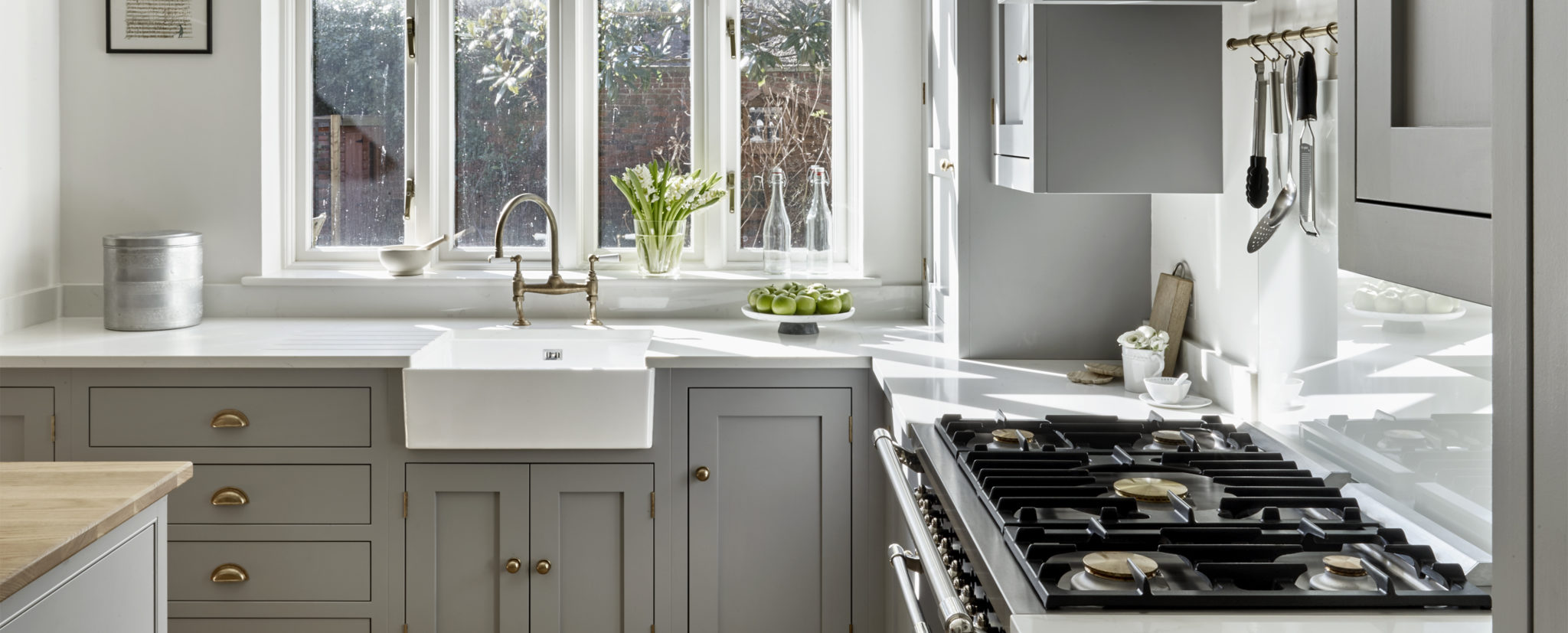 Butler sink and light grey country kitchen bespoke cabinets with antique brass handles