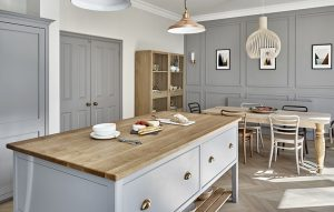 Open plan country kitchen diner with grey shaker style cabinets and oak worktops and chevron flooring.
