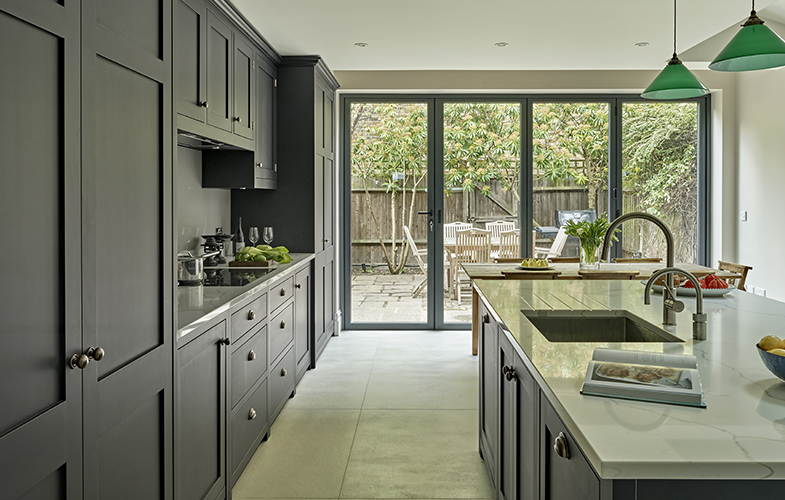Dark blue black shaker kitchen design with large island and folding glass doors