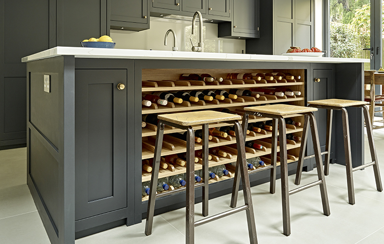 Dark shaker style island with integrated wine rack in light oak and science lab style stools