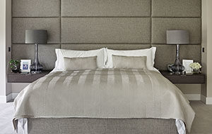 Upholstered headboard with floating bedside tables in grey dyed rippled sycamore