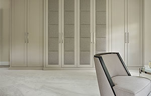 Fitted wardrobes in double silver by Zoffany with upholstered central panels for Luxury Master Bedroom design