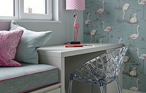 Study area with built-in desk and window seat with flamingo wallpaper