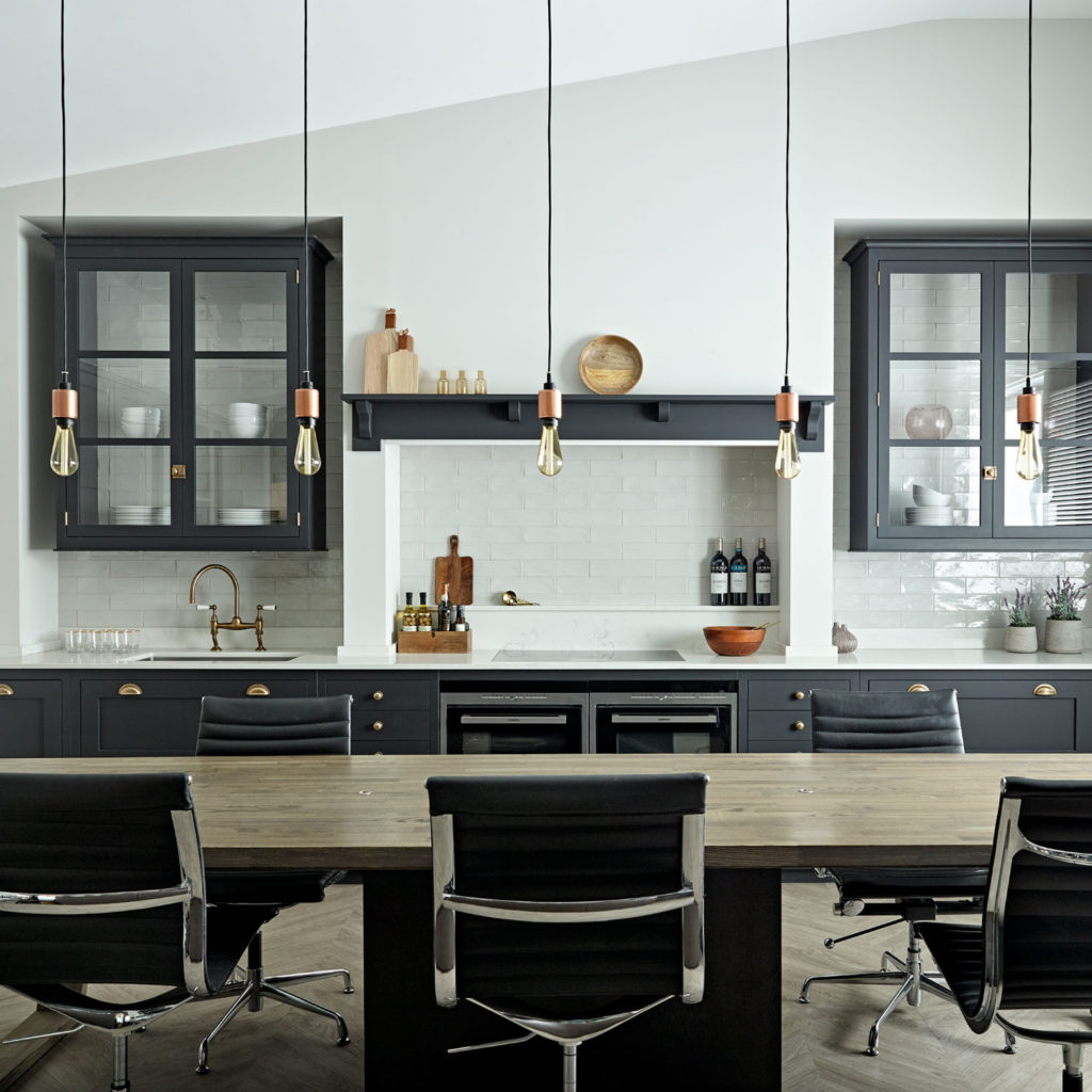 Inside the Brayer Design studio - display shaker kitchen design with dark grey cabinets and traditional brass knob and cup handles with vintage style copper pendant lighting