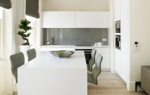 Contemporary compact kitchen for Kensington Apartment - white handleless minimalist kitchen and dining area
