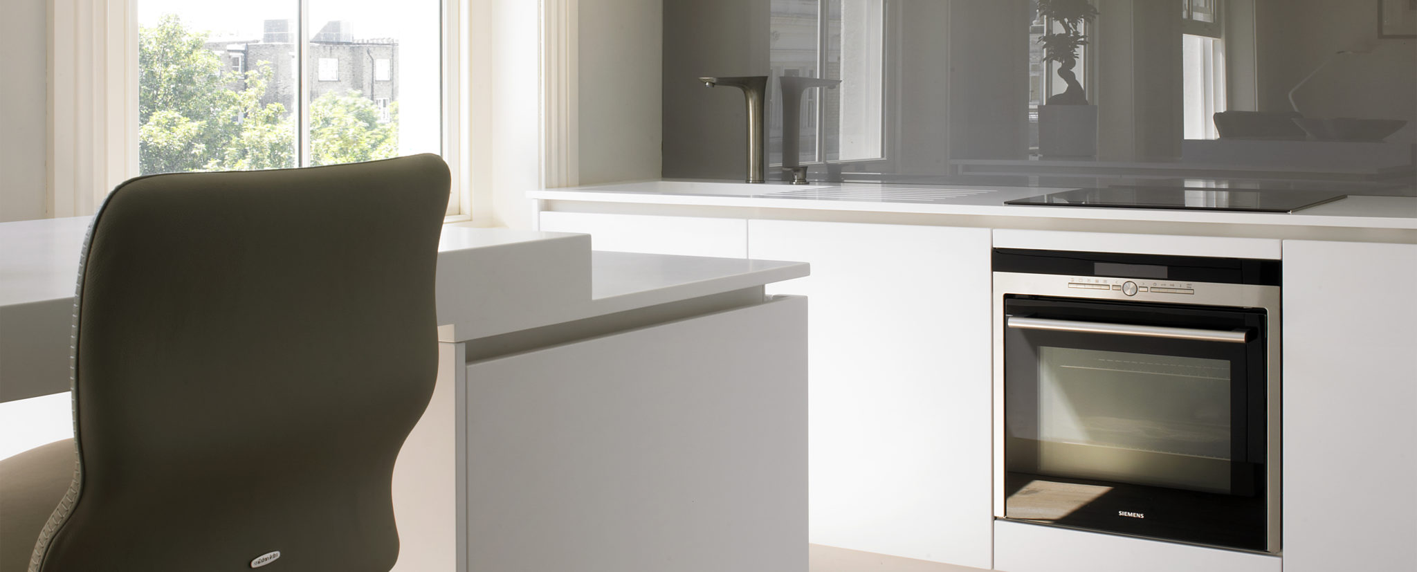 Compact Kitchen Design for Kensington Apartment. Minimalist white kitchen with mini island/breakfast bar.